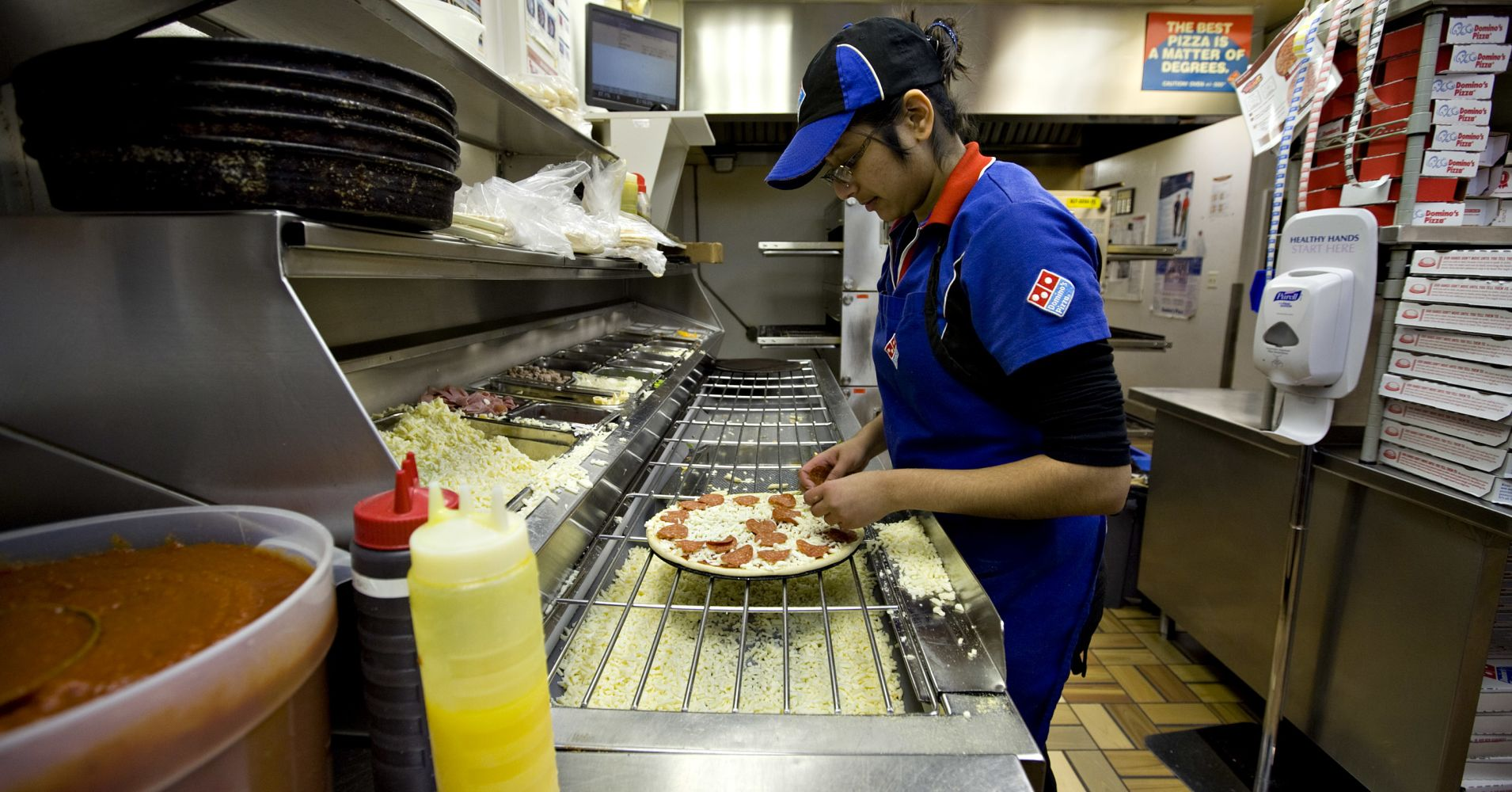 A worker puts pepperoni on a pizza inside a Domino's Pizza franchise in New York.