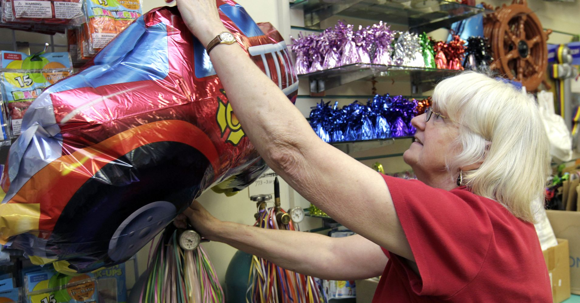 A woman fills a helium balloon for a customer in Raleigh, North Carolina.
