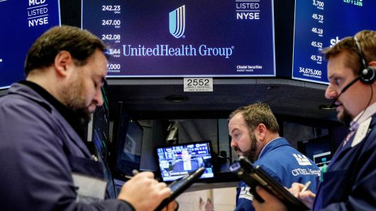 Traders work at the post where UnitedHealth Group is traded on the floor of the New York Stock Exchange.